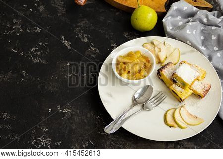 Sliced Pie On A White Plate With Pear Jam On A Black Table. Green Pears In The Background Are Blurre