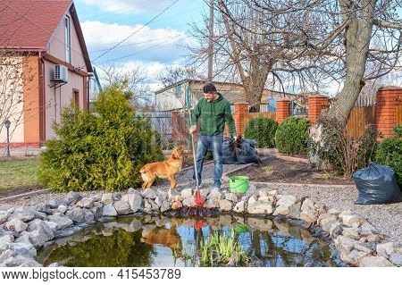 Mature Adult Caucasian Man Cleans A Garden Pond With Leaf Rake From Water Plants And Falling Leaves.