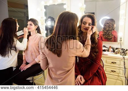 Make-up Artist Applying Bright Base Color Eyeshadow On Models Eye And Holding A Shell With Eyeshadow