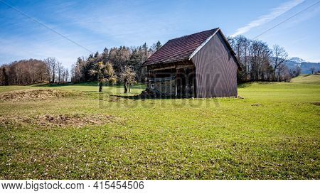 Barn In A Green Field Next To A Forest And Hill. Idyllic Landscape Scene In Switzerland. Tranquil Sc