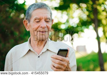 Grandfather With Mobile Phone In His Hand