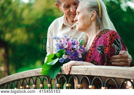 Embrace And Kiss Of Old Couple In A Park On A Sunny Day.