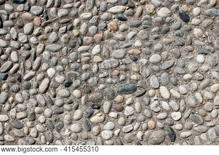 An Old Pebblestone Road Cobbled With Natural Stones As A Background