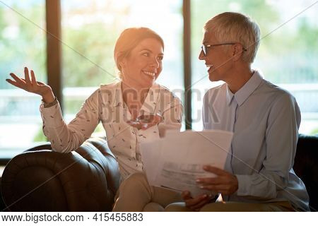 Young cheerful woman being mentored by female senior partner in the office