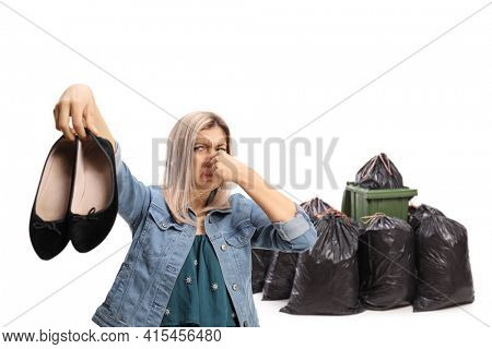 Young woman throwing a pair of smelly shoes in the garbage isolated on white background