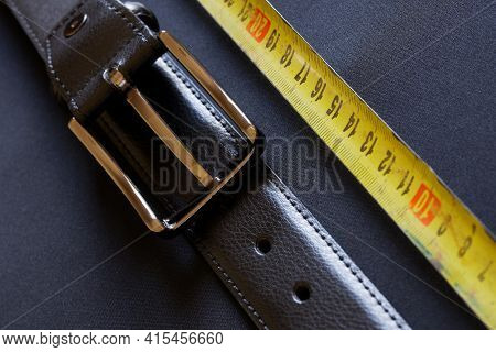A Black Leather Belt With Holes And A Metal Buckle Rests On A Gray Background Next To A Yellow Tape