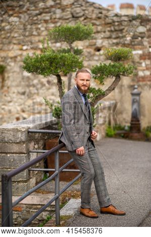 A Man With A Beard In A Strict Grey Three-piece Suit With A Tie In The Old Town Of Sirmione, A Styli