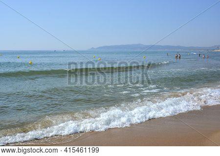 Spain L Estartit, July 3 2018. Gentle Sea Wave Pours Along The Shore With Calm Tides Rolling Along T