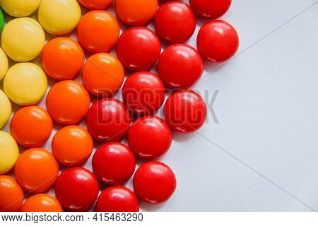 Rainbow Of Multicolored Sweet Candy Dragees On Isolated White Background. Decorative Creative Compos