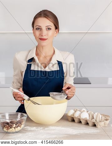 Yong Sweet Female Baker In Blue Apron Mixing  Batter In Big Bowl And Smiling. Process Of Making A Pi