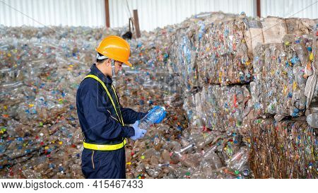 Engineer Checking Second Hand Plastic Bottles In The Background At Waste Recycling Factory,industry