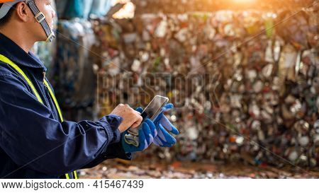Engineer Working At A Pile Of Scrap Metal Recycling And Recycling Industry.