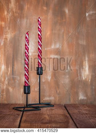 Black Candlesticks With Silver Burgundy Candles On Burgundy Brown Background