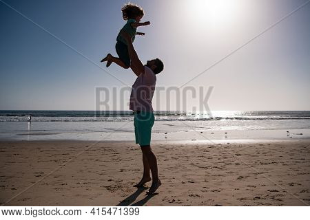 Father Throws Son Up Against The Blue Sky. Dad Throwing Child, Silhouette On Sunset. Concept Of Frie