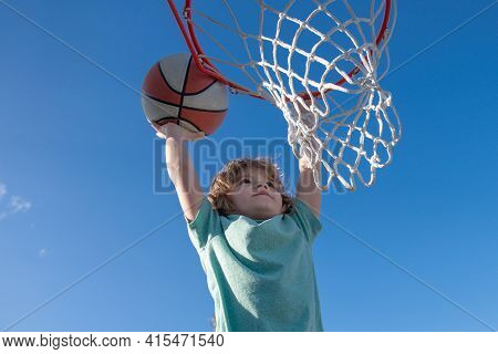 Basketball Slam Dunks Of Sporty Kids Basketball Player. Close Up Image Of Basketball Excited Kid Pla