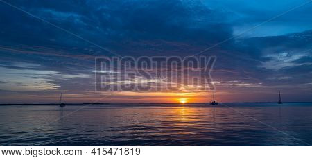 Boats On The Sea At Sunset. Sailboats With Sails. Ocean Yacht Sailing Along Water