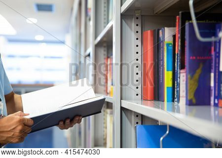 Man Reading A Book From Bookshelf In The School Library. Concepts For Read And Learn Education Or St