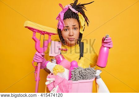 Dejected Unhappy Housemaid Has Braids Busy Doing Cleaning Of House Poses With Mop And Detergent Goin