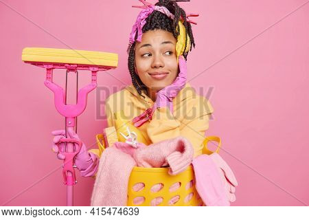 People Housework And Housekeeping Concept. Dreamy Housewife Keeps Hand On Face Being Deep In Thought
