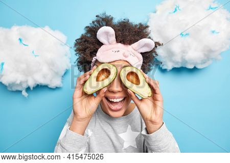 Joyful Curly Haired Woman Cover Eyes With Avocado Halves Recommends To Use Natural Organic Cosmetics