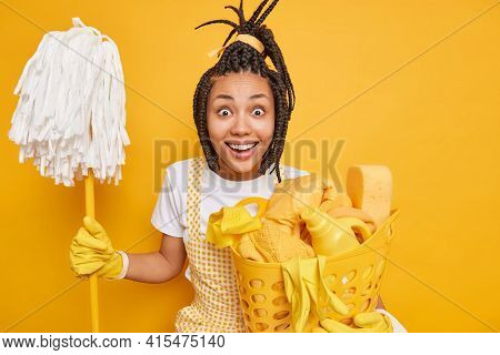 Positive Glad Afro American Woman Dressed In Apron Rubber Gloves Holds Mop For Washing Floor Holds B