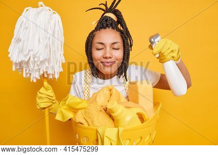 Hardworking Housewife Closes Eyes Smiles Pleasantly Enjoys Cleaning Holds Detergent And Mop Does Lau