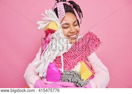 Pleased Young African American Woman Does Domestic Chores Embraces Cleaning Tools And Basin Of Laund