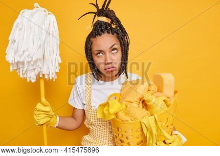Housework Concept. Unhappy Housewife Feels Tired Holds Mop Laundry Basket Does Housework Dressed In