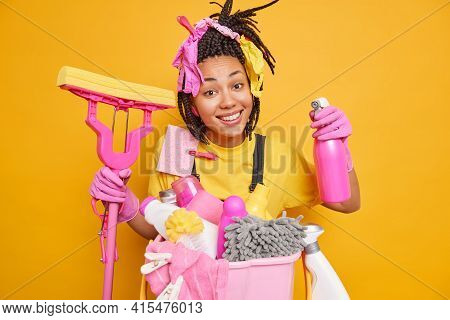 Home Cleaning Concept. Positive Dark Skinned Ethnic Woman With Dreadlocks Holds Detergent And Mop Do