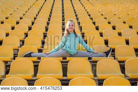 Happy Girl Gymnast Do Splits Stretching Legs On Stadium Seats, Gymnastics