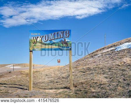Cheyenne, WY, USA - April 2, 2021: Welcome to Wyoming - road sign with some stickers added by travelers, highway 85 in early spring scenery.