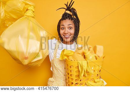 Smiling Afro American Woman With Dreadlocks Enjoys Housework Holds Polythene Bag Full Of Litter Bask