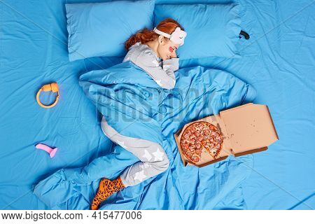 Top View Of Relaxed Redhead Woman Lies In Bed Under Soft Blanket Has Lazy Day Eats Pizza Awakes In G