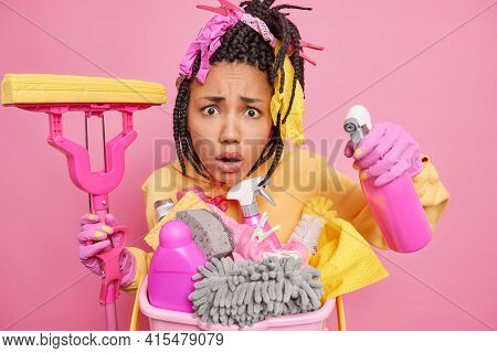 Indignant African American Woman With Dreadlocks Looks Displeased At Camera Holds Mop And Cleaning D
