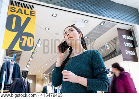 A Young Woman Communicates On The Phone. In The Background, There Is A Store And Posters With A Sale
