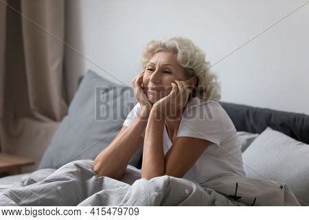 Happy Elderly Lady Awaking In Modern Comfortable Bedroom