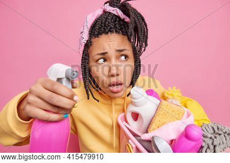 Household Housework And Chores Concept. Photo Of Puzzled Mixed Race Woman Holds Detergent For Washin