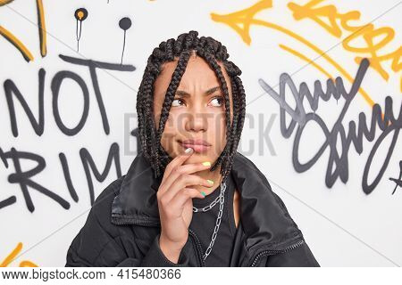 Street Style Teenagers Concept. Stylish Hipster Girl Has Dreadlocks Being Deep In Thoughts Keeps Han