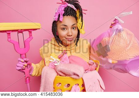 Housecleaning Concept. Satisfied Ethnic Woman With Rubber Gloves On Braids Holds Litter Bag And Mop