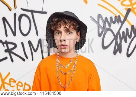Puzzled Youngster Looks Displeased At Camera Wears Hat Orange T Shirt And Chains Belongs To Youth Su