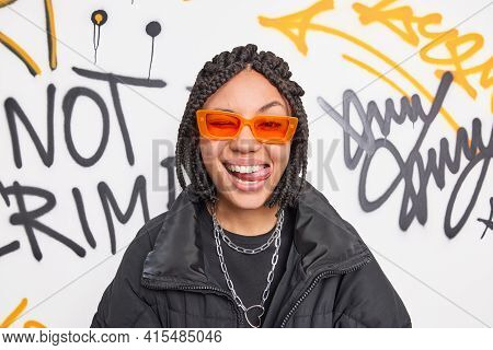 Cheerful Fancy Teenage Girl Wears Trendy Orange Suglasses And Black Jacket Sticks Out Tongue Has Dre