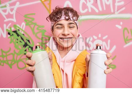 Positive Teenager Smiles Toothily Wears Braces On Teeth Closes Eyes Dressed In Hoodie Holds Two Spra