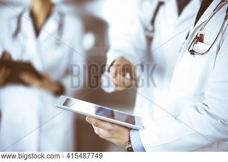 Group Of Unknown Doctors Use A Computer Tablet To Check Up Some Medical Names Records, While Standin
