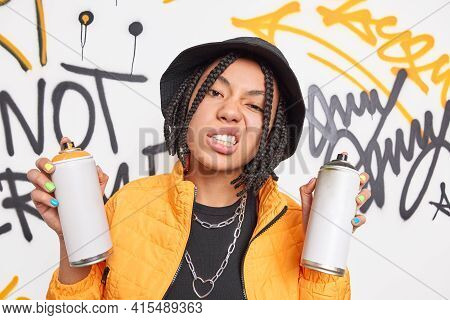 Cheeky Hipster Girl With Dreadlocks Clenches Teeth Smirks Face Holds Two Aerosol Sprays Wears Fashio