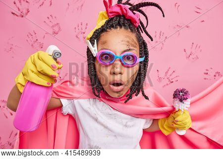 Stupefied Female Superhero With Dreadlocks Engaged In Household Chores Holds Cleaning Detergent And