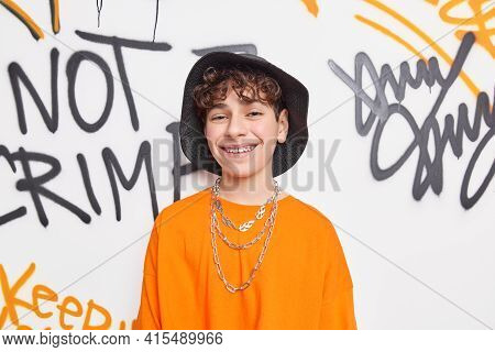Positive Male Teenager Wit Curly Hair Dressed In Street Style Clothes Smiles Broadly Wears Braces On