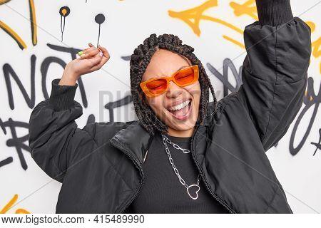 Upbeat Dark Skinned Woman With Dreadlocks Dances And Moves Energetically Wears Orange Sunglasses Bla