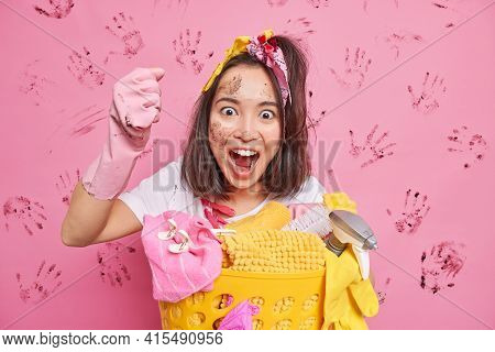 Untidy Housewife Exclaims Loudly Clenches Fist Does House Cleaning Poses Near Basket Of Laundry Has