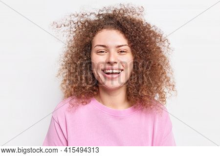 Horizontal Shot Of Cheerful Millennial Girl Smiles Broadly Shows Teeth Has Curly Bushy Hair Expresse