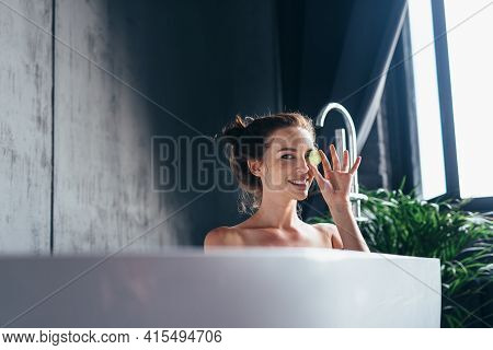 Woman Sits In The Bathtub And Holds A Piece Of Cucumber By The Eye.